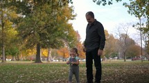 grandfather and granddaughter playing with fall leaves in a park
