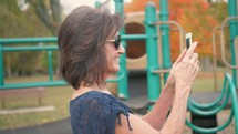 grandmother filming her granddaughter on the playground