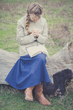 a girl praying over a Bible in her lap
