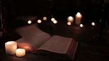 pages flipping on a Bible and flames from votive candles