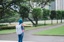 a woman with blue hair standing in a city with outstretched arms