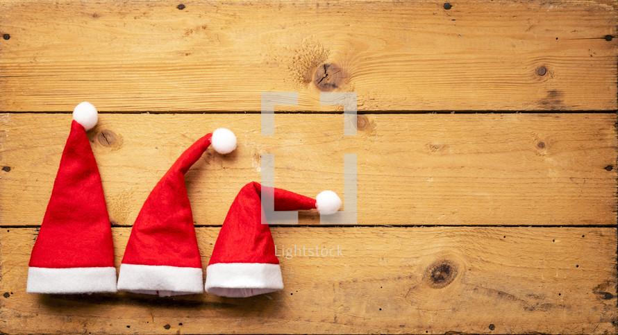 Santa hats on a wood background