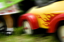 blurry image of wheels of a toddler's toy car and toddler legs