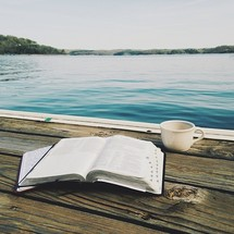 an open Bible and coffee mug on a dock