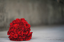 Bouquet of red roses on a grey cement background.