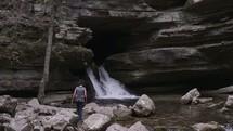 woman walking towards a waterfall