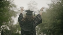 a graduate with hands raised in worship