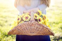 Girl holding basket of Yellow Flowers