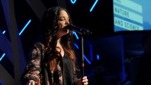 female worship leader singing on stage