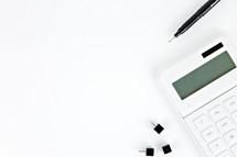 tacks, pen, and calculator on a white desk
