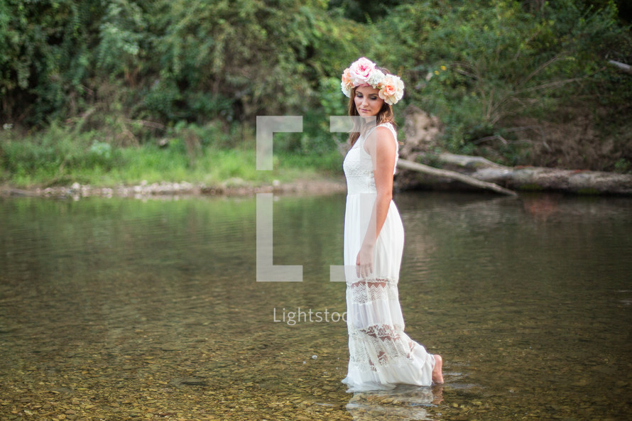 a woman in a white dress and flowers in her hair walking in water