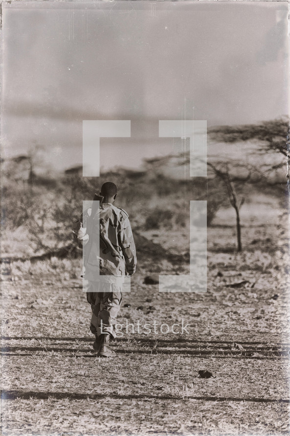 soldier with a gun walking through the desert