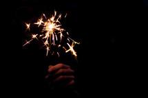 hand holding a sparkler in darkness