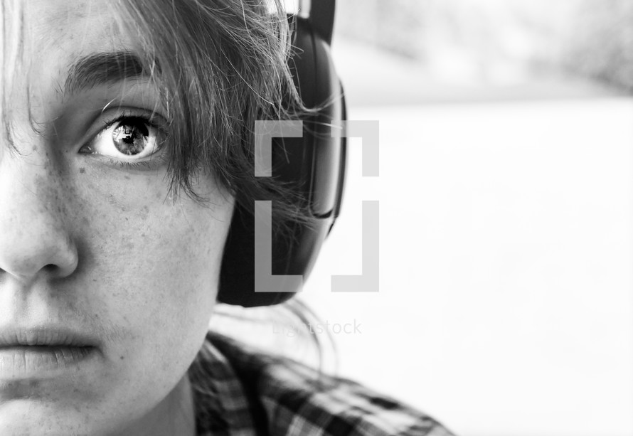 a child with freckles listening to headphones