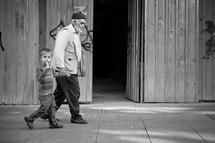 Grandfather and grandson walking on sidewalk