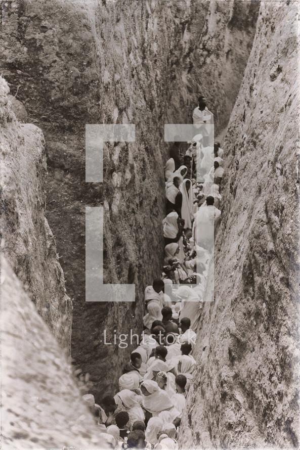 crowd of people in a narrow crevice heading towards a celebration