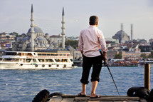 man fishing on a dock across from a mosque