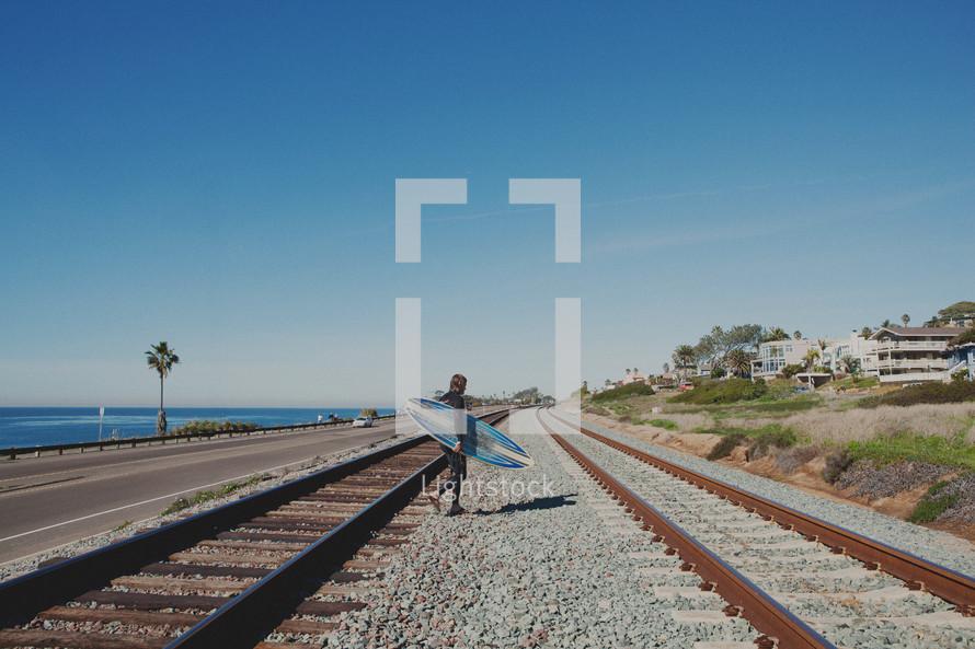 surfer walking with surfboard across railroad tracks