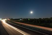 Speeding highway traffic at night.