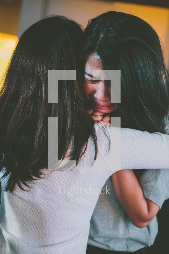 women hugging at a worship service