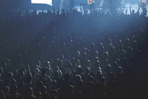spotlights shining on a crowd at a concert
