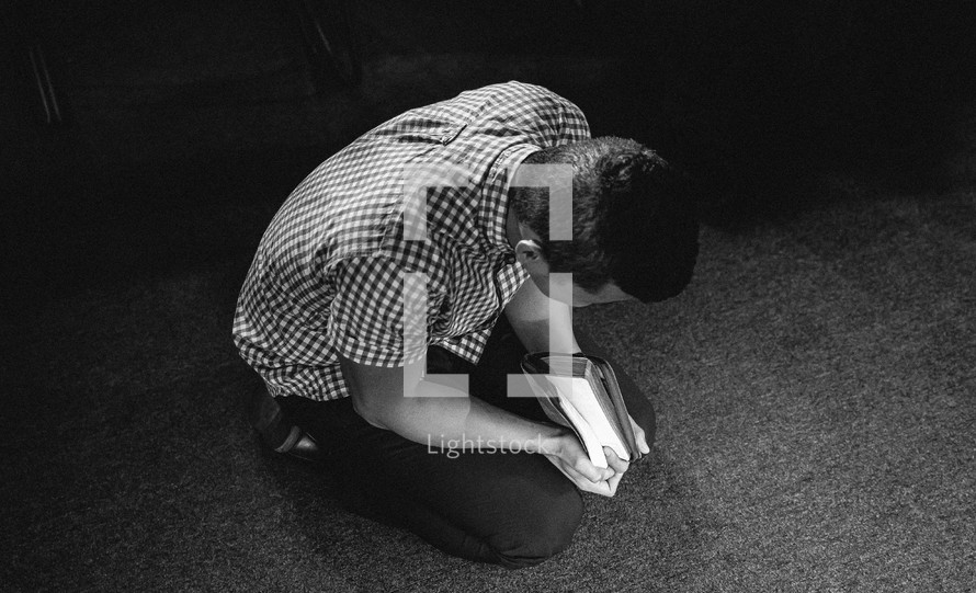 Kneeling with the bible on his hands