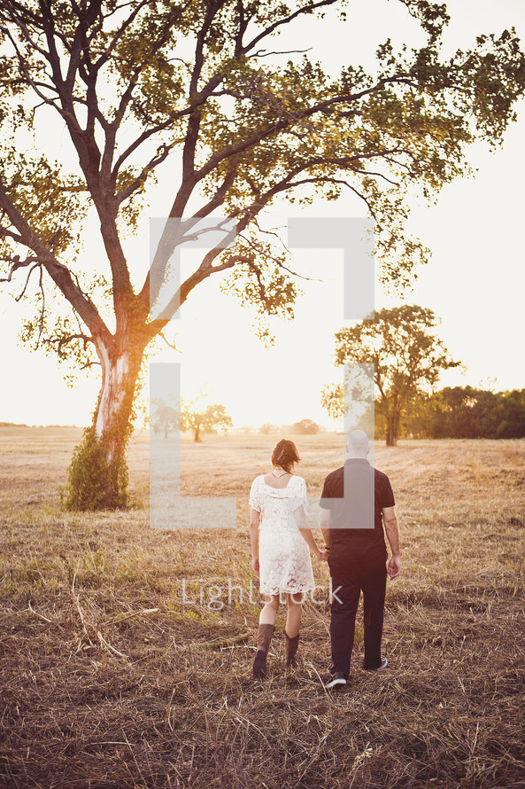 couple walking hand in hand through a field