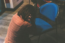 a woman kneeling in prayer over a chair