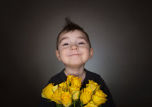 smiling boy holding a bouquet of yellow roses