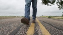 feet of a man walking on the center lines of a road