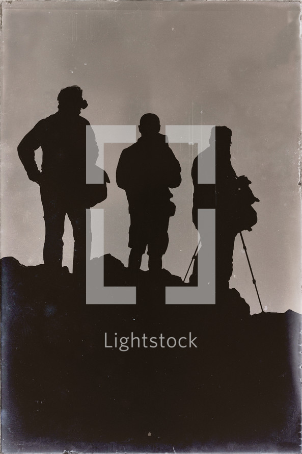 silhouettes of tourists holding camera