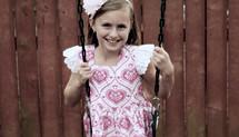 little girl on a swing set
