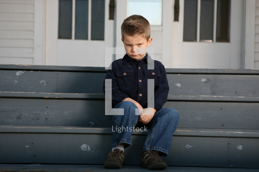 pouting boy sitting on stair steps