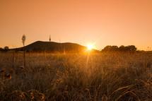 sun setting behind a hill