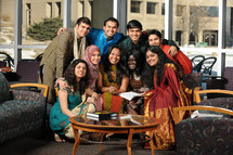 Group of young people posing for a picture, all of different ethic backgrounds, in a waiting room