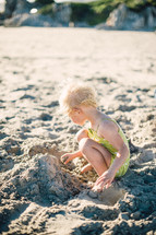 toddler girl in a bathing suit playing in the sand