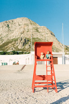 siblings sitting in a lifeguard stand on a beach