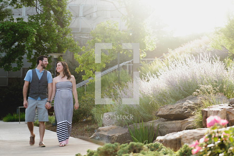 an expecting couple walking holding hands