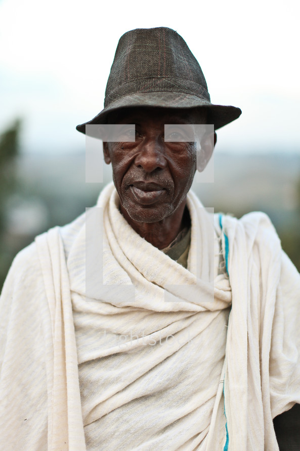 man wearing a hat and a blanket