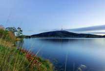 A placid lake with hills and a tower in the distance.