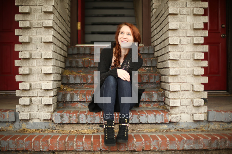 a teen girl sitting on brick stairs