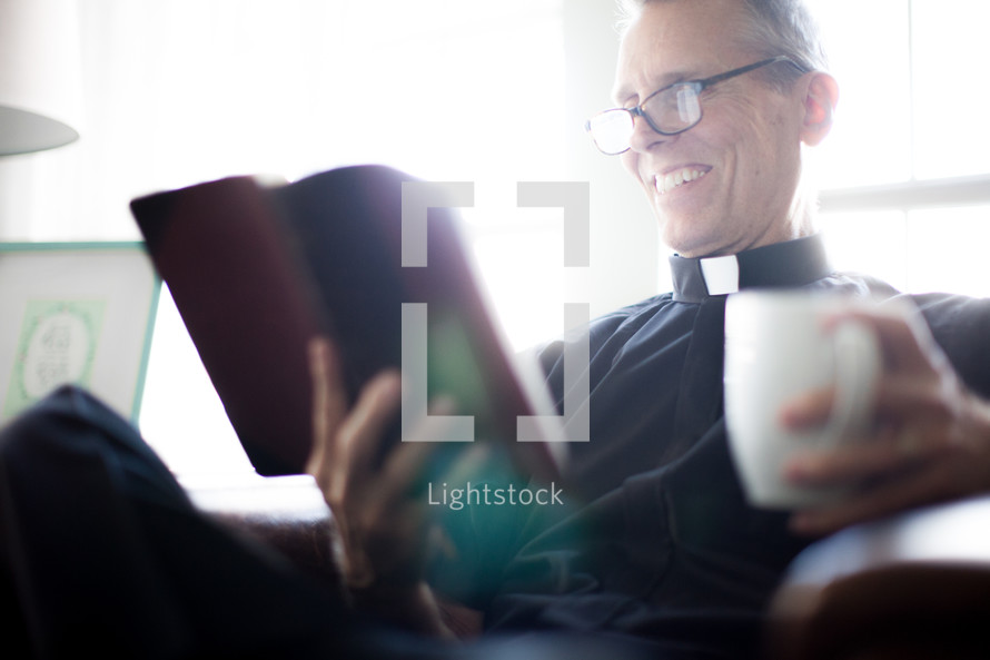A minister sitting and reading a Bible with a cup of coffee.