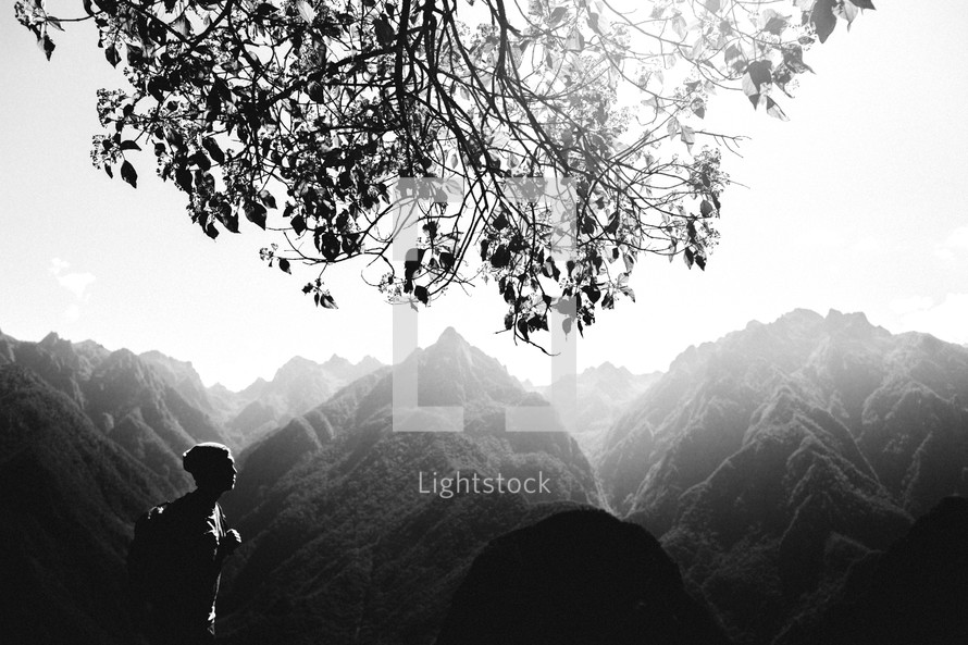 Silhouette of a man hiking through the haze-covered mountains.
