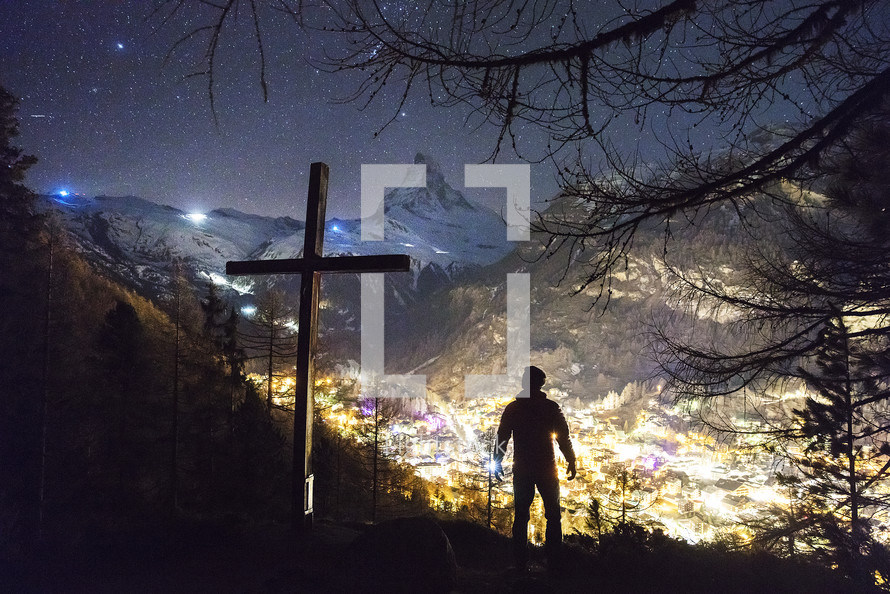 man standing next to a cross looking down at lights in a valley