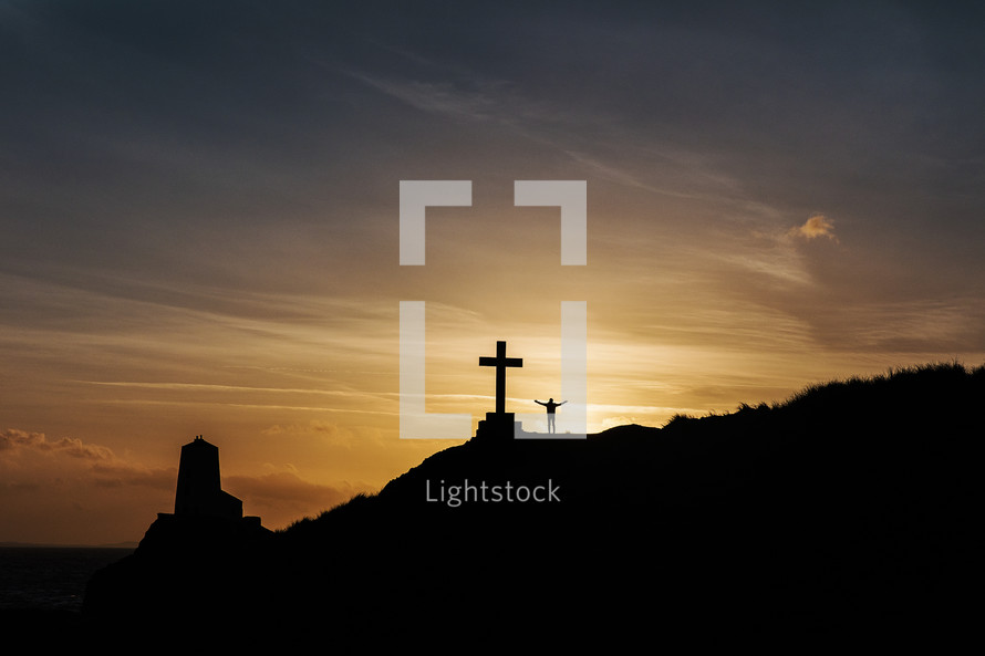 silhouette of a man standing next to a cross with open arms