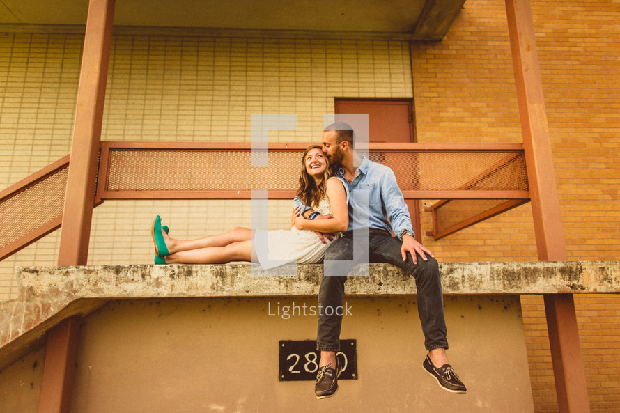 couple sitting and hugging on a ledge