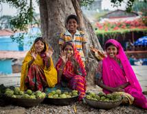 children waving in India