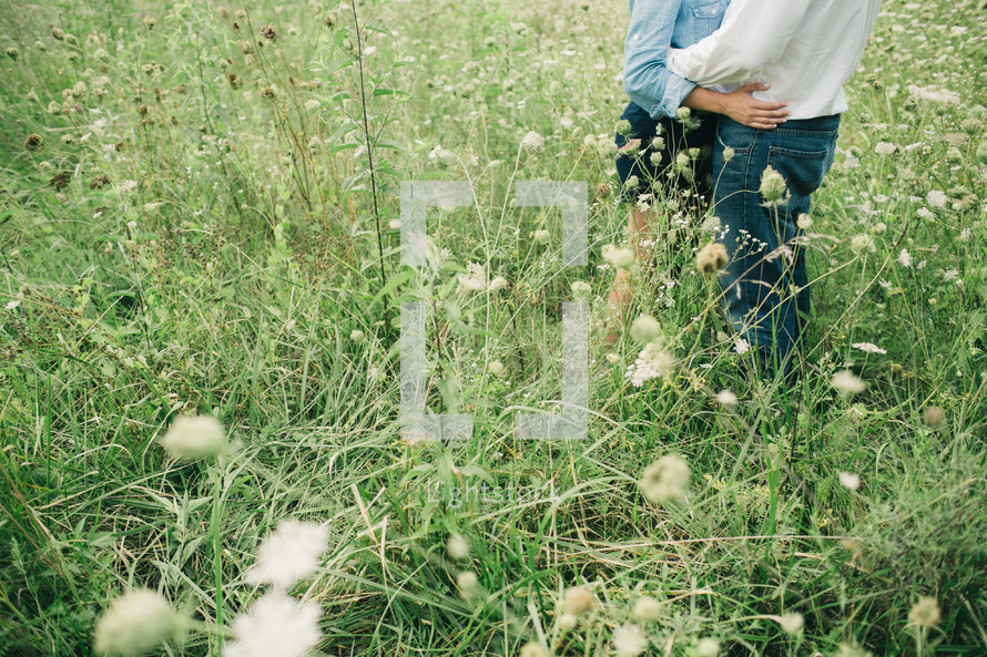 a couple embracing in a field of tall grasses