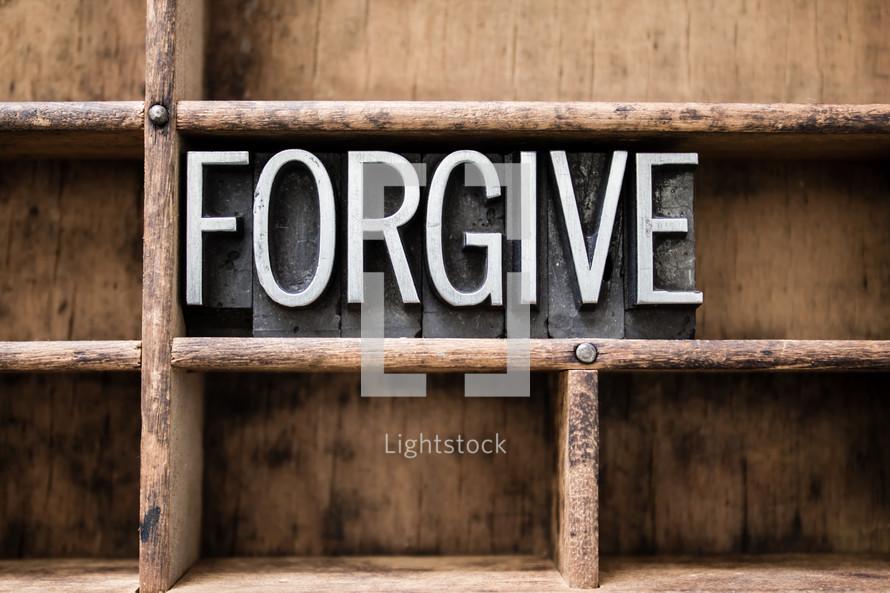 word forgive in blocks on a bookshelf