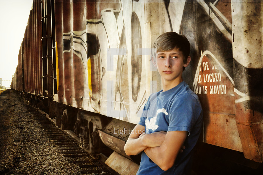 A teenage boy leans up against a train